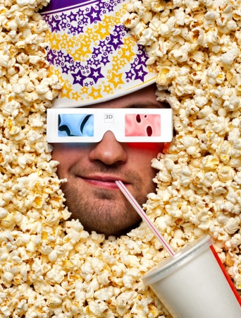 theater popcorn: Happy face in popcorn with bucket on head watching 3D movie and drinking soda Stock Photo