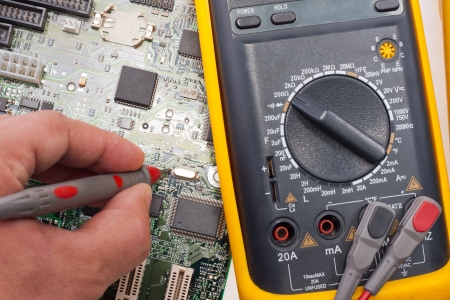 Computer engineer examining motherboard circuit by multimeter photo
