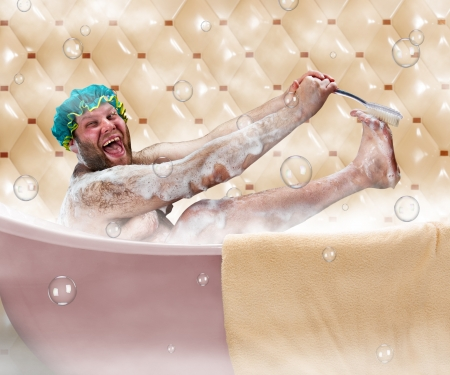 Bizarre ugly man washing his leg in a bath photo