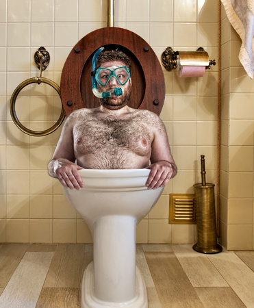 scuba goggles: Bizarre man with goggles swimming in vintage toilet