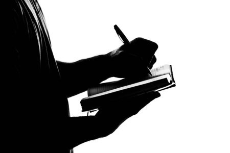 Silhouette of man writing business diary. Isolated on white photo