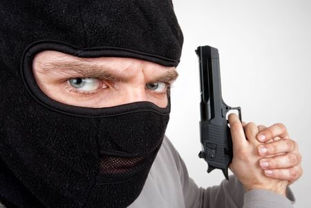Close-up of serious armed criminal with gun Stock Photo - 18477725