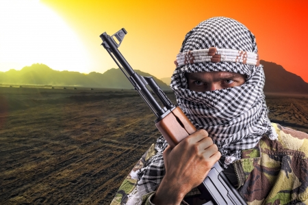 Portrait of serious middle eastern man with AK-47 in desert at sunset Stock Photo - 18482619