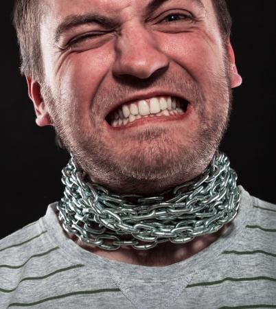 restraining: Screaming man with iron chain around neck Stock Photo