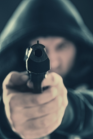 Serious gangster is aiming a gun to you Stock Photo - 18550182