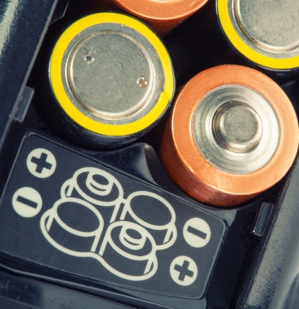 plus symbol: Loading batteries into a electronic device