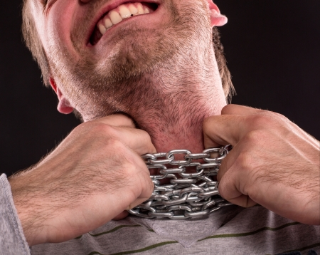 symbol victim: Stressed man with iron chain around neck Stock Photo