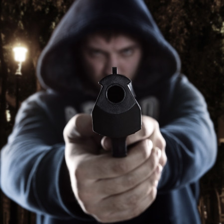 Serious gangster is aiming a gun to you Stock Photo