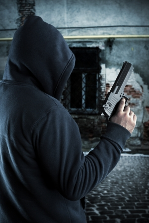armed: Gangster with gun in ghetto at night Stock Photo