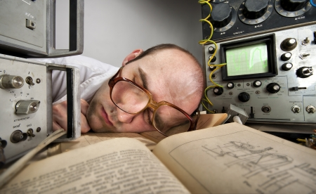 Exhausted scientist sleeping on book at vintage technological laboratory photo