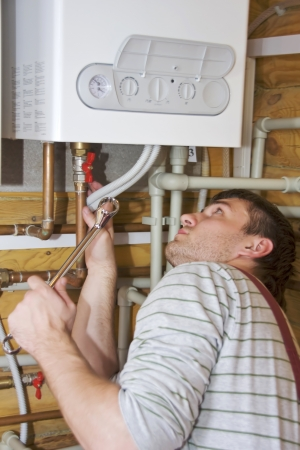 Plumber at work. Servicing gas boiler Stock Photo - 18560791
