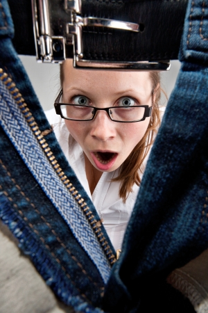 Surprised young girl looking inside unzipped man's pants photo