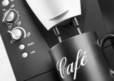 Espresso pouring into black cup from coffee machine photo