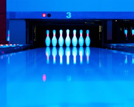 Ten bowling pins at the end of alley. Ultraviolet luminosity photo