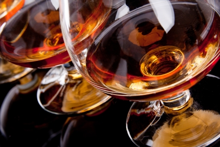 cognac: Three glasses of cognac in a row Stock Photo