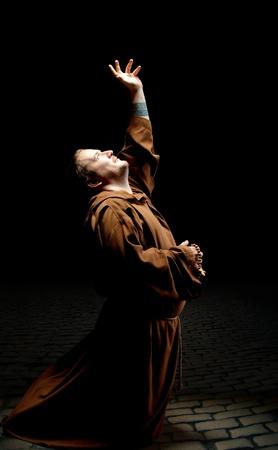 arrodillarse: Monk de pie en arrodilla y pide ayuda a Dios