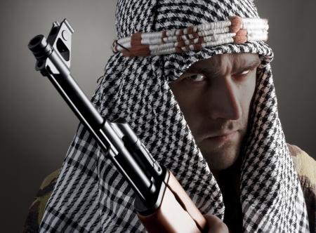 hombre disparando: Retrato de hombre serio de Oriente Medio con AK-47