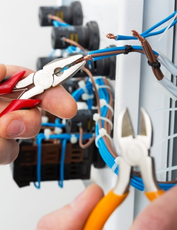 fusebox: Hand of an electrician with tools at an electrical switchgear cabinet Stock Photo