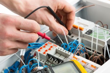 ingeniero electrico: Las manos de un electricista con sonda multímetro en un armario de distribución eléctrica