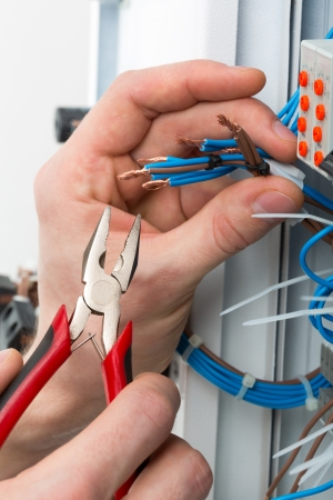 electricista: Las manos de un electricista con herramientas en una caja de conexiones eléctricas