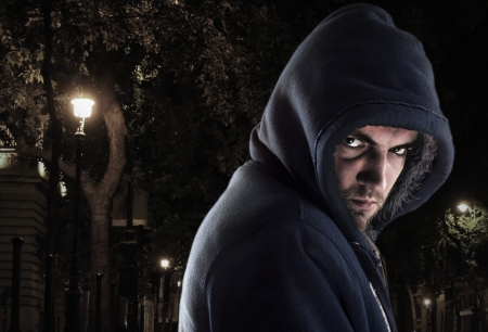 hoodlum: Serious bandit in ghetto at night looking to you Stock Photo