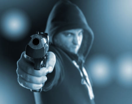 Serious gangster is aiming a gun to you. Toned in blue photo