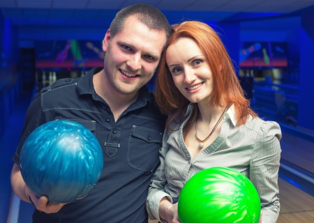 Happy couple in a bowling alley having fun photo