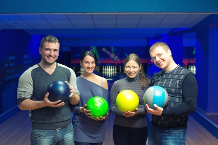Group of four friends in a bowling alley having fun photo