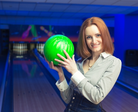 Beautiful woman in a bowling alley having fun photo