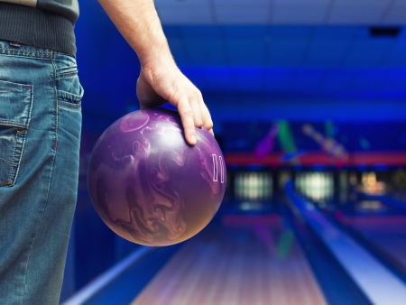 Man holding ball against bowling alley photo