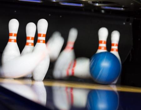 bowling alley: Bowling ball hitting motion blurred pins Stock Photo