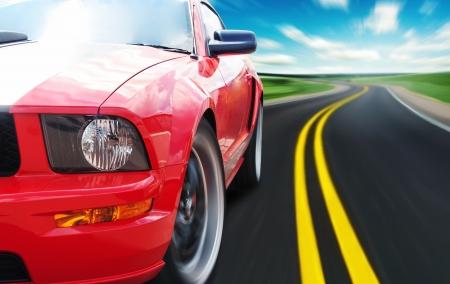 Coche deportivo rojo por un camino estrecho