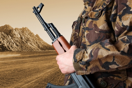 man holding gun: Soldier holding rifle AK-47 against desert Stock Photo