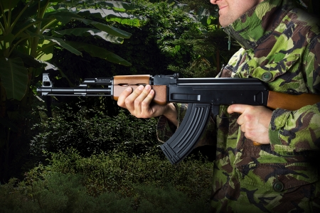 Soldier with rifle AK-47 in jungle photo