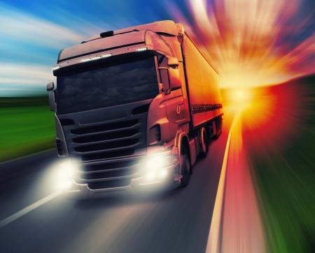 remolque: Cargo exceso de velocidad de camiones en la carretera en el ocaso