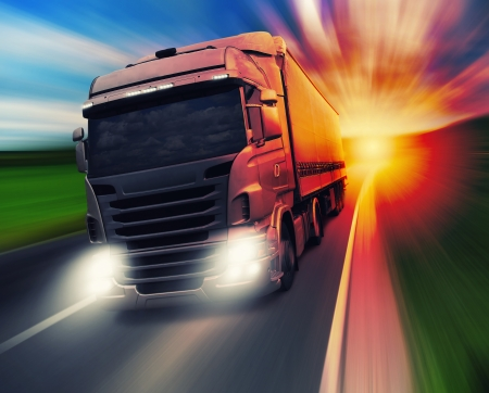 Cargo truck speeding on highway at sundown Stock Photo
