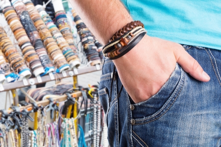 wrist cuffs: Closeup of a male standing with leather bracelet on his hand