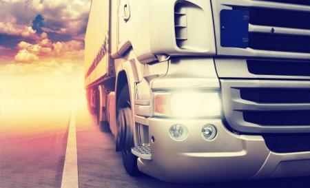 """ciężarówka: Cargo truck prÄ™dkoÅ›ci na zachodzie sÅ'oÅ""""ca na autostradzie Zdjęcie Seryjne"""