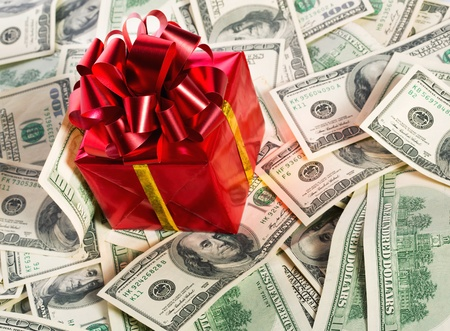 Red gift box on heap of $100 dollar bills photo