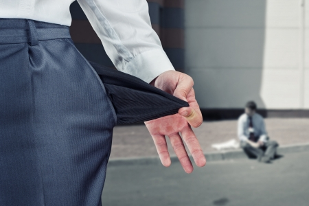 Businessman pulling empty pocket out of pants photo