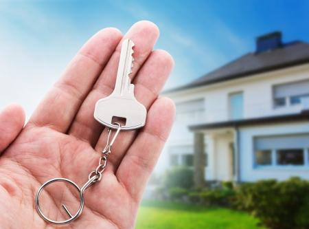 garden key: Key in hand against new house Stock Photo