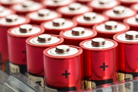 Many red AA batteries in a row photo