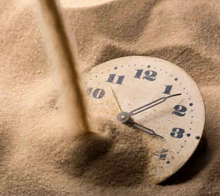 Sand pouring on old clock face photo