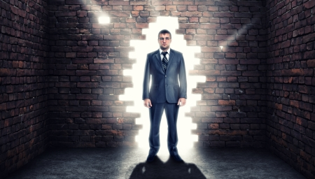 Coming confident businessman standing in wall hole photo