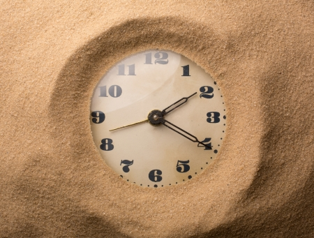 Old alarm clock in sand photo