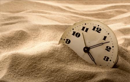 Oude gezicht van de klok in het zand Stockfoto