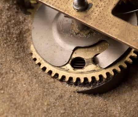 hardiness: Mechanical endurance - clock gears in sand Stock Photo