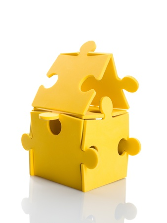 puzzling: Jigsaw puzzle pieces make a house. Isolated on white