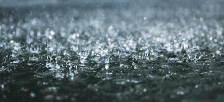 дождь: Капли проливного дождя на воде Фото со стока