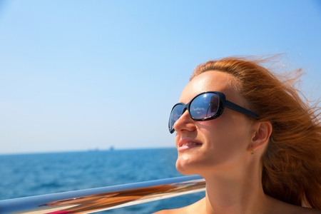 Young woman in sunglasses is relaxing on yacht photo
